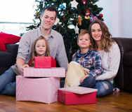 Young family members presenting gifts on Christmas. At home Royalty Free Stock Images