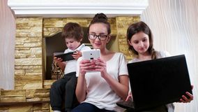 Young family members socializing at home using electronic devices, teen girls and small brother stock video footage
