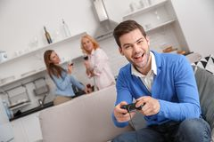 Young family with mother-in-law at home weekend guy playing game royalty free stock image