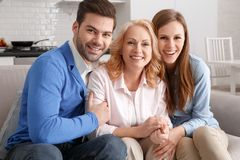 Young family with mother-in-law at home weekend hugging smiling royalty free stock photos