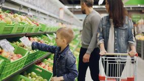 Young family mom, dad and little boy are choosing fruit in supermarket touching and smelling them and putting in trolley. Shopping for food together and people stock video