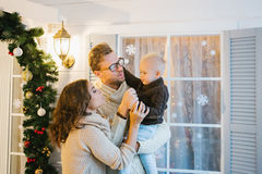 A young family - mom, dad and son stand next to the window  Stock Photos