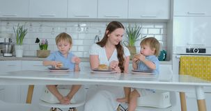 Young family mom and two sons sitting in the kitchen at the white table eating burgers together and having fun. Kids stock video footage