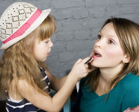 Young family mother and daughter make up at mirror Royalty Free Stock Images