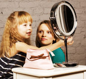 Young family mother and daughter make up at mirror Stock Photo