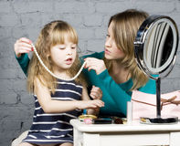 Young family mother and daughter make up at mirror Royalty Free Stock Image
