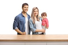 Young family of a mother, father and a baby girl posing behind a wooden counter. Isolated on white background royalty free stock photography