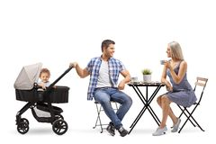 Young family of a mother, father and a baby in a stroller sitting in a cafe royalty free stock photo