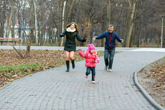 Young Family Mother Father Little Baby playing in park. Young Family Mother Father Little Baby playing in Autumnal park Smiling and Joyful running on paved alley Stock Photo