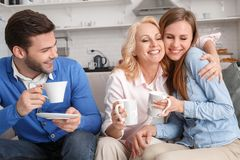 Young family with mother-in-law at home weekend drinking coffee. Young family men and women with mother-in-law hugging daughter at home weekend sitting on sofa Stock Photography