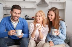 Young family with mother-in-law at home weekend drinking. Young family men and women with mother-in-law at home weekend sitting on sofa drinking hot tea looking stock photo