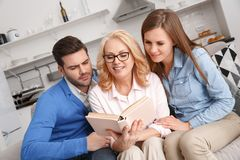 Young family with mother-in-law at home weekend reading intereresting story. Young family men and women with mother-in-law at home weekend sitting on sofa Royalty Free Stock Photo