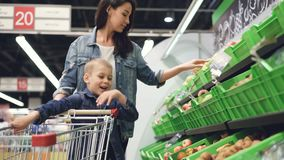 Young family mother and son are buying fruit in grocery store, they are taking pears and kiwifruit and putting them in. Trolley. Happy customers, people and stock video