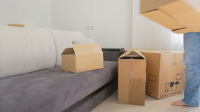 Young family moving out of their old apartment and carrying boxes from the room. Young family moving out of old apartment and carrying boxes from the room stock footage
