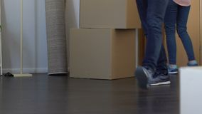 Young family moving to new apartment, carrying boxes with stuff, buying property stock video footage
