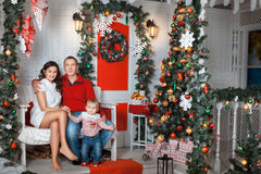 Young family near the Christmas tree. Young family sitting in the decoration of the room near the Christmas tree Royalty Free Stock Photography
