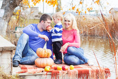Young family near lake with pumpkins, autumn time Stock Image