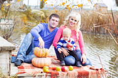 Young family near lake with pumpkins, autumn time Royalty Free Stock Photo