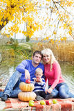 Young family near lake with pumpkins, autumn time Stock Photo