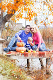 Young family near lake with pumpkins, autumn time Royalty Free Stock Photography