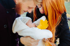 Young family and newborn son in autumn park Royalty Free Stock Photography