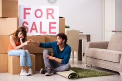 The young family offering house for sale and moving out. Young family offering house for sale and moving out royalty free stock photography