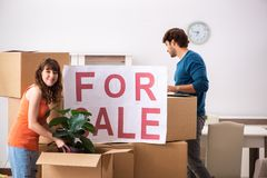 The young family offering house for sale and moving out. Young family offering house for sale and moving out stock photo