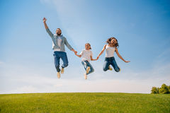 Young family with one child holding hands and jumping on meadow Royalty Free Stock Photo
