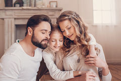 Young family with one child sitting embracing together at home Stock Images