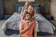 Young family with one child sitting together and hugging in bedroom Royalty Free Stock Photos