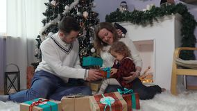 Young family opens Christmas presents stock footage