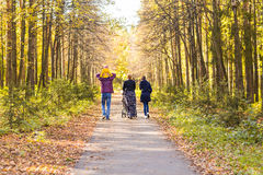 Young Family Outdoors Walking Through Autumn Park Royalty Free Stock Photos