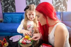 Young family painting Easter eggs -Mother and daughter Royalty Free Stock Image
