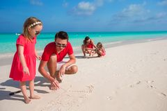Young family painting on the sand during vacation Royalty Free Stock Photos