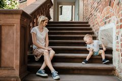 Young family. Parents sit with their son on the stairs. Mom and dad and your baby. Little boy. Young family. Parents sit with their son on the stairs. Mom and royalty free stock photo