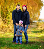 Young family, parents with small children in golden autumn city park stock image