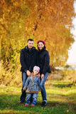 Young family, parents with small children in golden autumn city park stock images