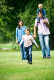 Young Family in Park. Young family running outdoors smiling Stock Photo