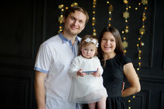 Young family is photographed in Christmas holiday. Royalty Free Stock Image