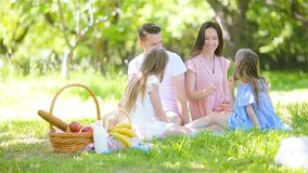 Happy family on a picnic in the park on a sunny day. Young family on picnic in cherry garden stock video