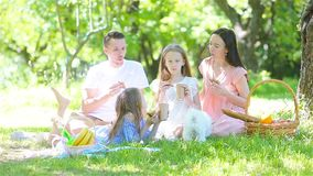 Happy family on a picnic in the park on a sunny day. Young family on picnic in cherry garden stock footage