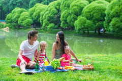 Young family on a picnic by the lake in park Royalty Free Stock Image
