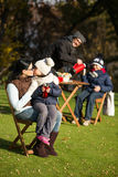 Young family on a picnic. Mother kissing her little daughter white she is holding a cup of tea. Father and his son drinking tea or coffee on the background Royalty Free Stock Photo