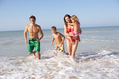 Young family play on beach. In the sun Royalty Free Stock Photo