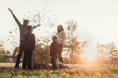 Young family playing with autumn leaves standing in a circle in Royalty Free Stock Photos