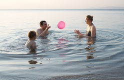 Young family playing with ball at sunset Stock Photography