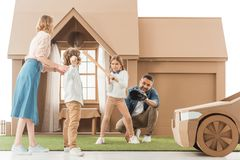 young family playing baseball together on yard of cardboard house
