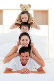 Young Family playing on bed together Royalty Free Stock Image