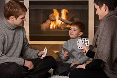 Young family playing card game. Young family with 4 years old kid playing card game at home in a cold winter day Stock Photos