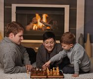 Young family playing chess. Young family with 4 years old kid playing chess at home in a cold winter day Royalty Free Stock Photos